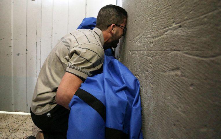 Een Palestijnse vader met het stoffelijk overschot van zijn dochter, omgekomen bij een Israëlische luchtaanval. Beeld AFP