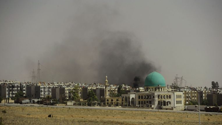 Een zwarte rookpluim na een aanval van regeringstroepen op Adra al-Omalia. Beeld reuters