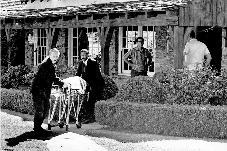 Het levenloze lichaam van Sharon Tate wordt weggevoerd van haar villa aan de Cielo Drive in Los Angeles.  Beeld AP
