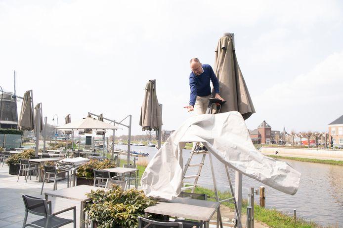 Patrick Wolffenbuttel, een van de eigenaren van De Zon haalt zet de parasols op. Volgende week mag het terras weer open. Weliswaar van 12.00 tot 18.00, maar toch.