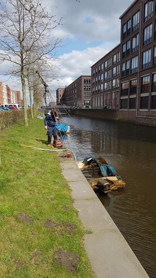 Bas Willing haalt een halfgezonken bootje boven water.
