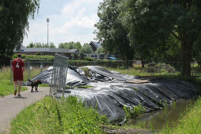 Het vervuilde gebied aan de Otto van Reesweg is afgeschermd met hekken en de grond ligt, voorlopig afgedekt met plastic zeilen, opgeslagen.
