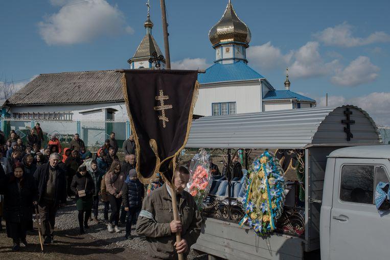 Inwoners van Bar sluiten zich aan bij de processie voor soldaat Roeslan Slisarenko. Zijn kist staat achter in de grijze wagen.   Beeld Emile Ducke