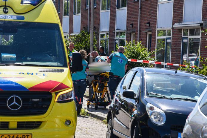 Een zwaargewonde vrouw wordt naar de ambulance gebracht na de steekpartij aan de Karel Doormanstraat in Bodegraven.