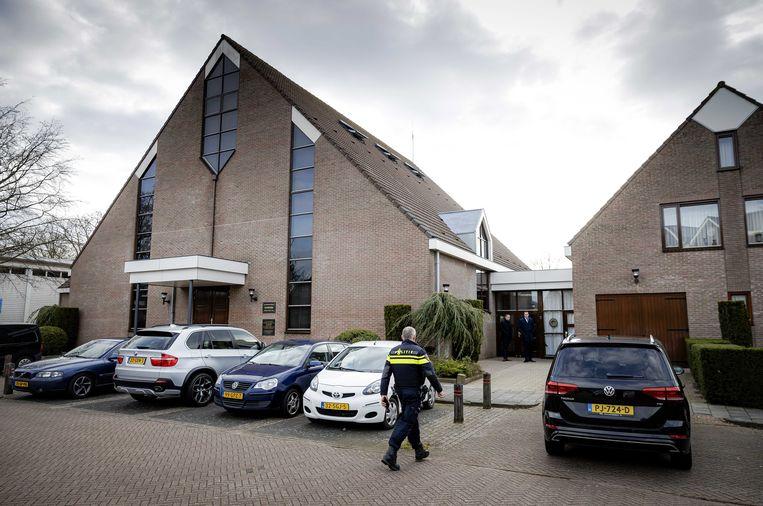 Een politieagent bij de Sionkerk in Urk die heeft besloten de beperkende landelijke coronamaatregelen op te heffen zodat het gebouw weer volledig is opengesteld voor kerkgangers. Beeld ANP