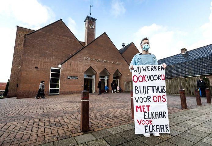 Zorgverlener Chris voert actie tegen de fysieke kerkdienst bij de ingang van de Rehoboth Kerk in Barneveld.