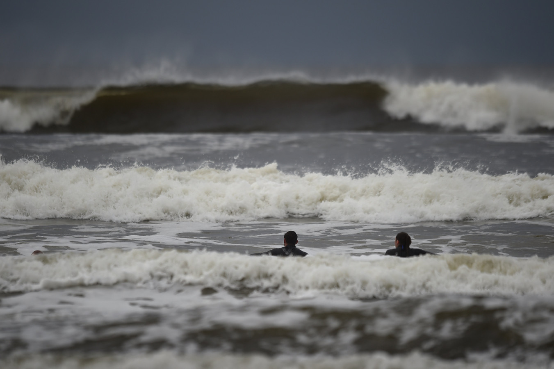 Surfers genieten van de hoge golven op de dag voordat orkaan Ophelia de Ierse kust bereikt.