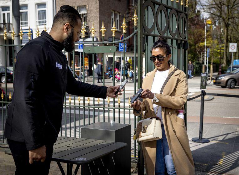 Een bezoeker toont een negatief testbewijs bij de entree van Artis.  Beeld EPA