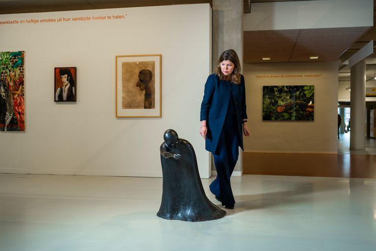 Sandrine van Noort bij een zwart bronzen beeld van Henk Visch. Mensen vinden het griezelig; het doet ze denken aan de dood die je meelokt naar een andere wereld.  Beeld Jiri Büller