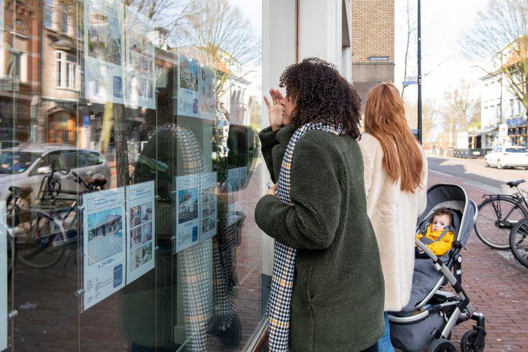 Woningzoekers kijken bij een makelaar in de etalage.  Beeld Hollandse Hoogte / Patricia Rehe