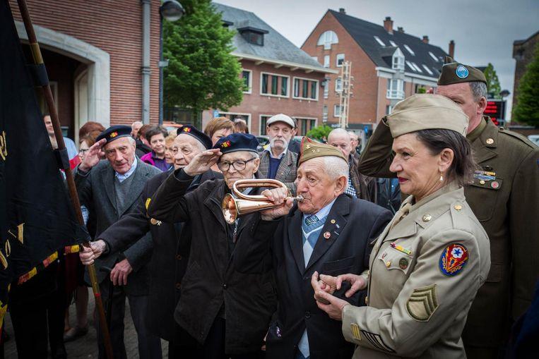 Een dame houdt de hand vast van Alfons Pauwels, terwijl hij de Last Post blaast aan het Sint-Martinusmonument.