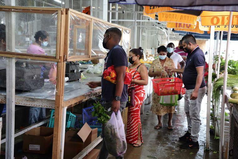Surinamers in de rij bij een winkel tijdens de lockdownperiode. In Suriname werd in mei een totale lockdown afgekondigd. Beeld ANP