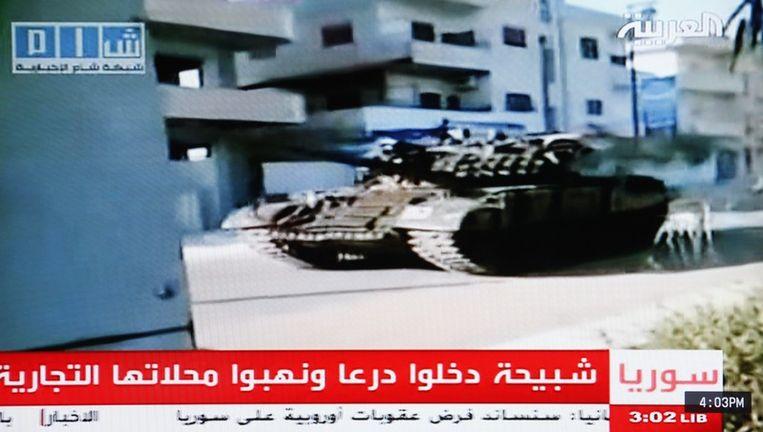 Een beeld uit een nieuwsuitzending van Al Arabiya: een Syrische tank rijdt door de straten van de stad Deraa. Beeld epa
