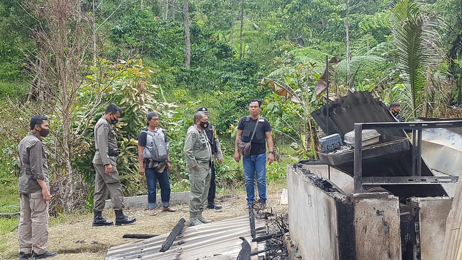 De politie inspecteert de afgebrande huizen in het dorp Lemban Tongoa.
