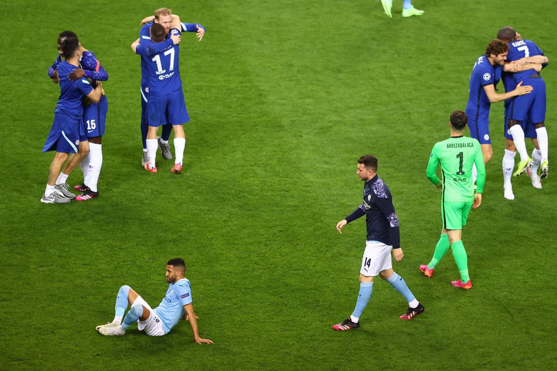 Riyad Mahrez zit verslagen op de grond, terwijl de spelers van Chelsea de triomf in de Champions League-finale vieren.  Beeld AFP
