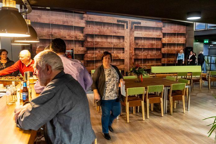 Levendigheid in de centrale hal van de multifunctionele accommodatie, die aan de bar grenst. De fanfare pauzeert tijdens een repetitie voor een decor van sluisdeuren.