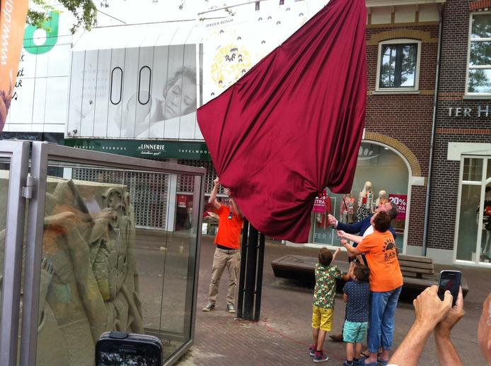 Regelaar Daniëlle van Tilburg, wethouder Frank den Brok en zijn kinderen en zandkunstenaar Jos de Ruig openen de Zandsculpturenroute bij het gerepareerde werk op het Walplein in Oss.