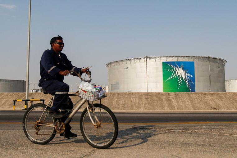 Een werknemer fietst langs een grote opslagtank van Saudi Aramco, het staatsoliebedrijf van Saudi-Arabië. Met Rusland en de VS vormt Saudi-Arabië de topdrie op de lijst van grote olieproducenten.  Beeld REUTERS