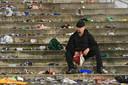 Een eenzame supporter blijft na de nederlaag achter tussen het afval. Dat was het dan...