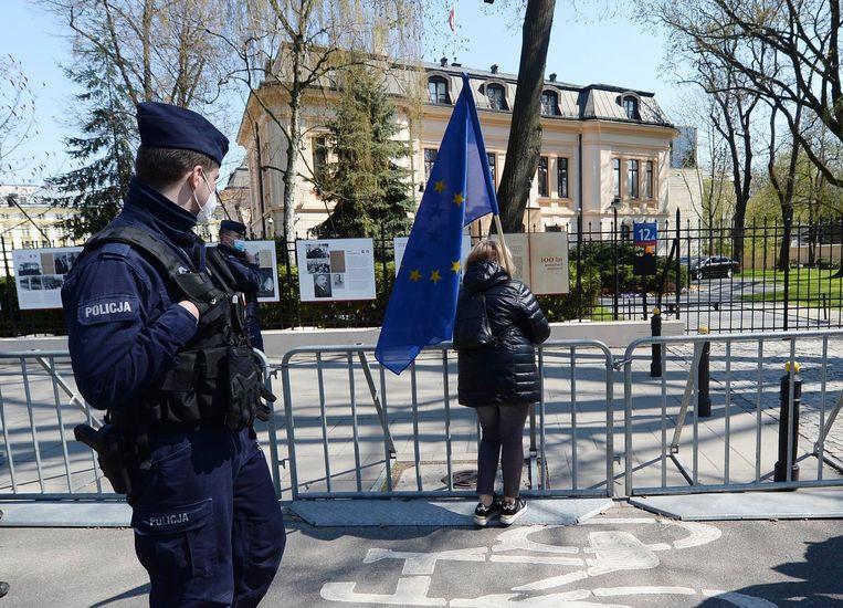 Een vrouw met een Europese vlag voor het Constitutionele Hof in Warschau. Beeld AP