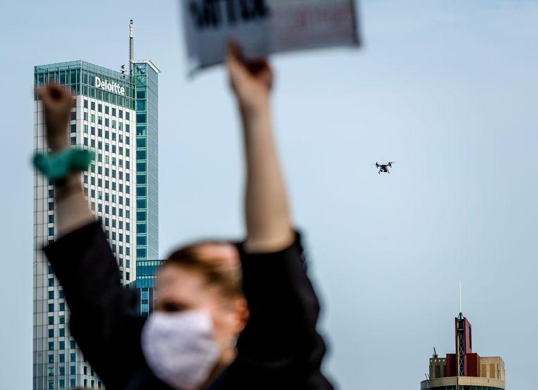 Een drone met luidspreker van de politie roept om om 1,5 meter afstand te houden tijdens een manifestatie in Rotterdam. Deze week werd bekend dat de politie nog meer drones gaat kopen. Beeld Hollandse Hoogte / ANP