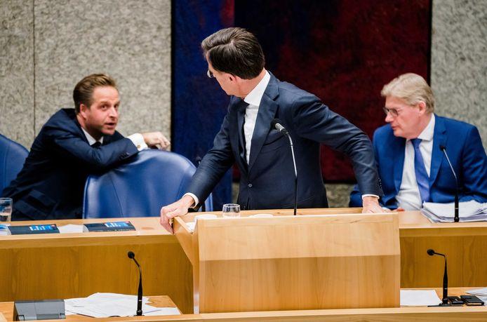 Een onderonsje tussen premier Rutte, minister De Jonge (VWS) en minister Van Rijn (Medische Zorg) vandaag tijdens het coronadebat