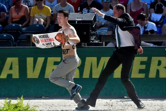 Een beveiliger houdt een 'streaker' tegen tijdens het EK paardensport in Rotterdam.