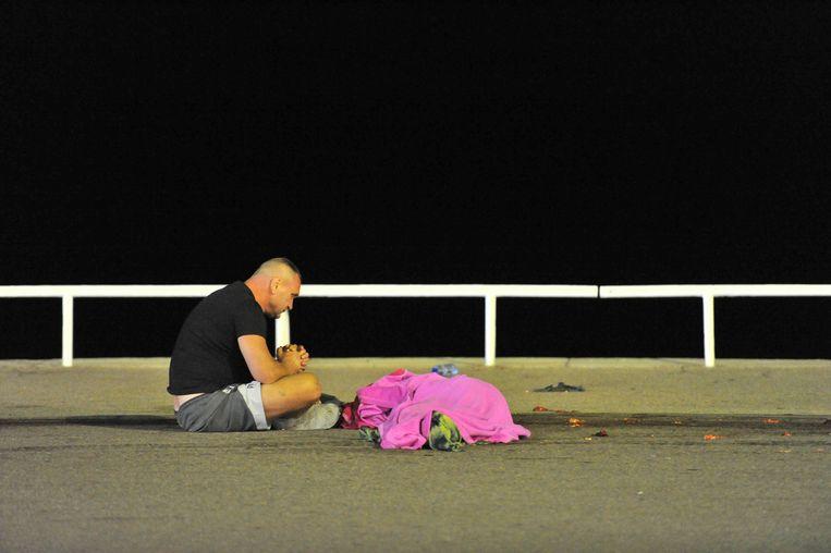 Een man rouwt bij een van de overledenen. Beeld Photo News