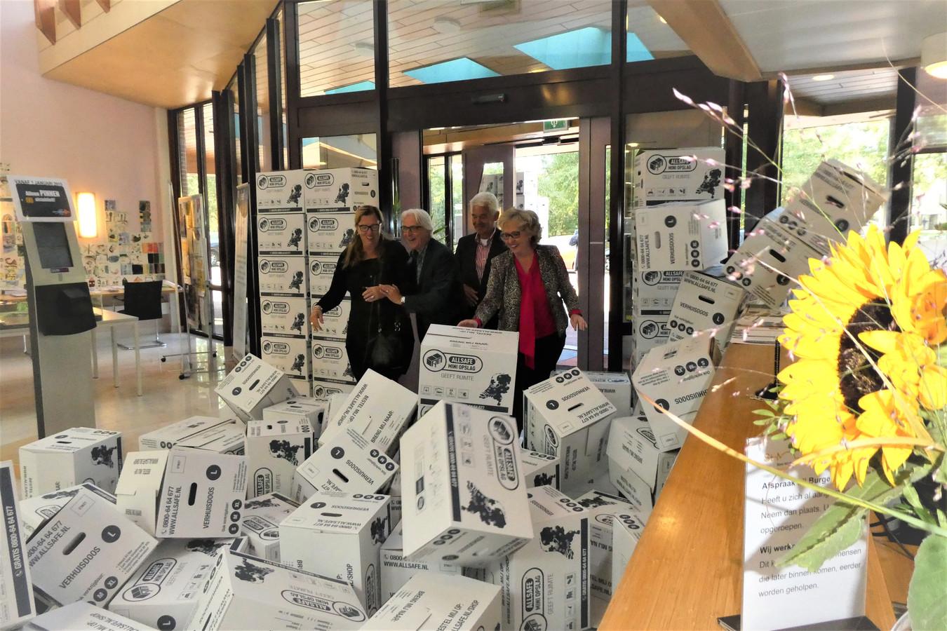 V.l.n.r. Rita van de Wouw (Bint), Martin Hol (bibliotheek Brenthof), Henk van Hemmen (De Huif) en wethouder Lianne van der Aa duwen verhuisdozen weg bij de ingang van het gemeentehuis in Sint-Michielsgestel.