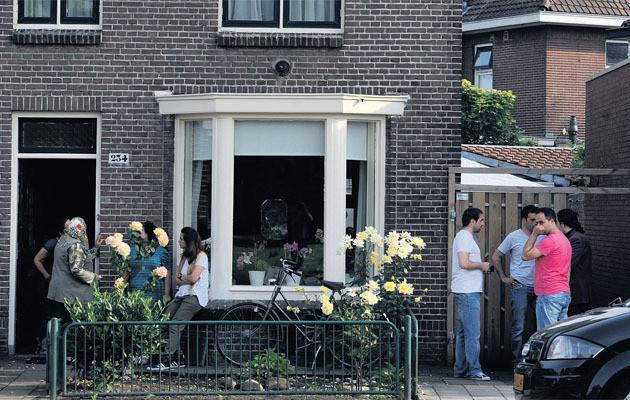 Familie, vrienden en collega's rouwen om het overlijden van Aziz bij zijn woning.