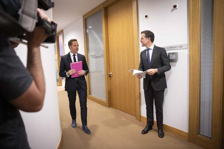Demissionair premier Mark Rutte en demissionair minister Hugo de Jonge maken zich op voor een persconferentie over de coronamaatregelen. Beeld EPA