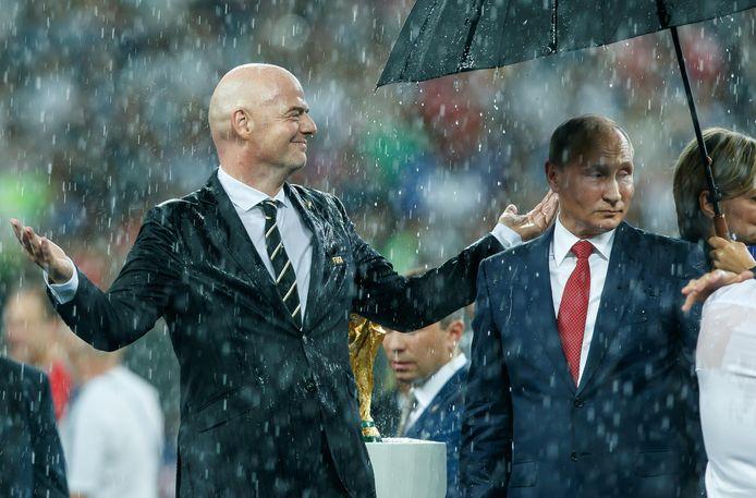 Infantino staat bij de uitreiking van de wereldbeker in de regen, de enige paraplu is voor Poetin.
