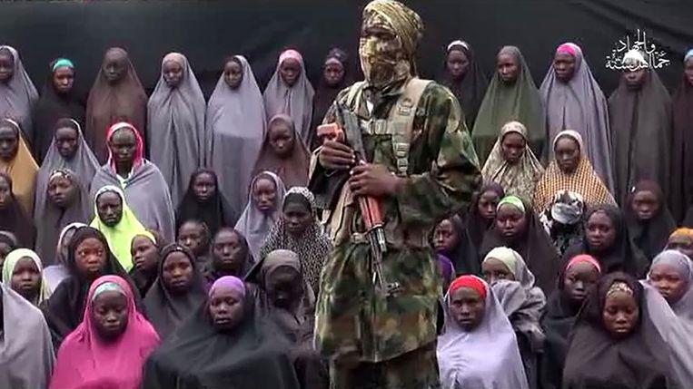 Een gemaskerde Boko Haram-strijder houdt een toespraak voor de ontvoerde meisjes.  Beeld AFP