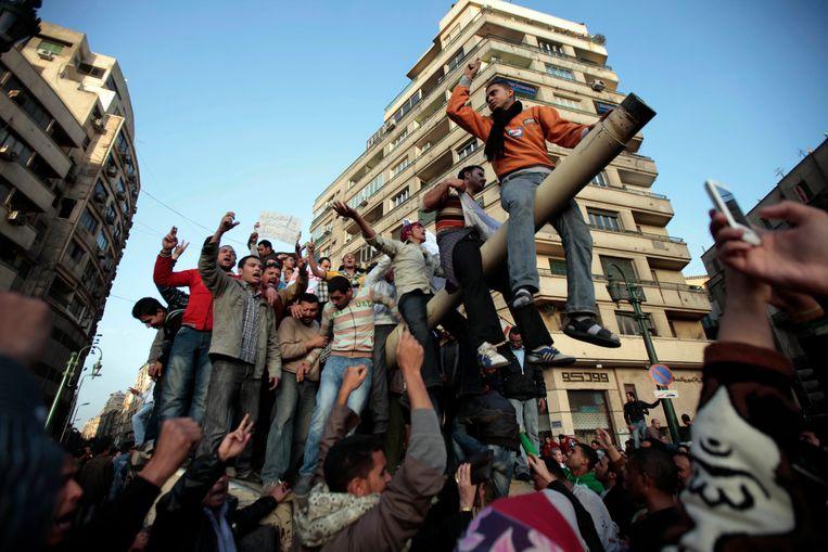 Demonstranten op de loop van een Egyptische tank. Beeld AP