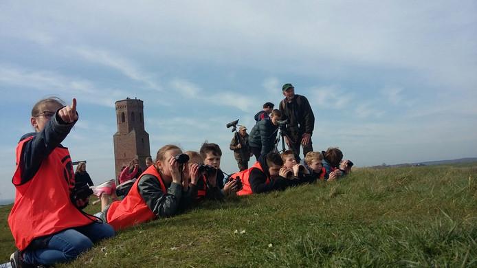 Leerlingen van de Kirreweie uit Burgh-Haamstede spieden op Buitenlesdag op een afstandje naar lepelaars bij de Plompe Toren.