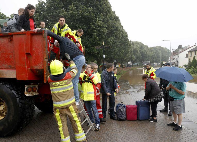 De brandweer helpt met de evacuatie van mensen uit hun woningen door de wateroverlast in Zuid-Limburg.  Beeld ANP