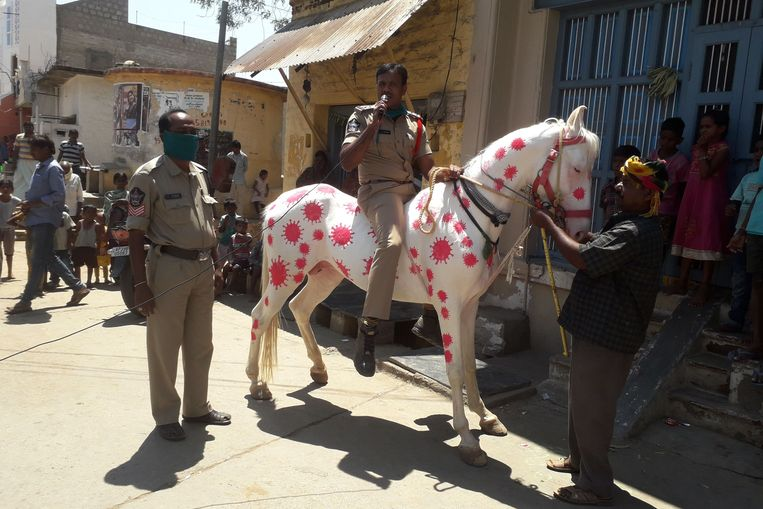 Een politieman rijdt op een paard met 'coronavlekken', en probeert zo de bevolking uit te leggen dat ze binnen moeten blijven. Beeld AFP