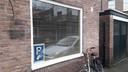Protest met posters voor het raam tegen betaald parkeren in Breda.