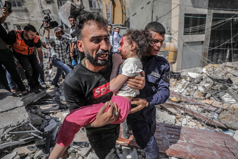Een Palestijn haalt zijn gewonde dochter weg uit het puin van een huis na een Israëlische raid op Gaza-stad. Beeld EPA