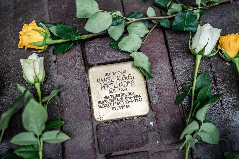 Naast de Stolperstein van verzetsman Karel Pekelharing werden na de plaatsing rozen gelegd. Beeld Joris van Gennip