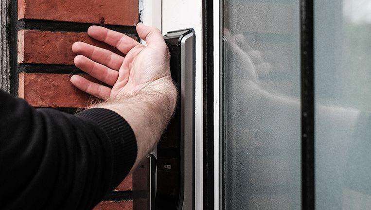 Een man ontgrendelt zijn voordeur met een ingeplante chip. Beeld Bob Van Mol