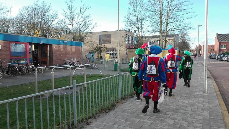 De zwarte pieten van de Zwarte Pieten Actiegroep op weg naar basisschool De Cirkel in Zuilen, die ze binnenvielen om vervolgens pepernoten en stickers uit te delen.