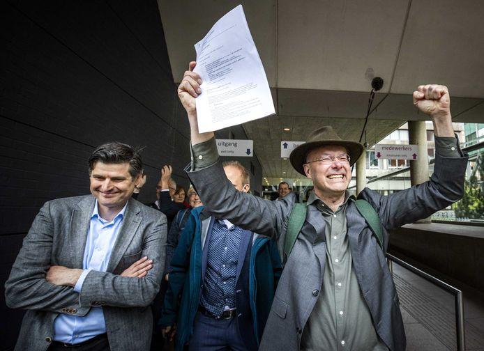 Advocaat Roger Cox (L) en directeur Donald Pols van Milieudefensie  na de overwinning in de klimaatzaak tegen Shell, op 21 mei bij de rechtbank in Den Haag.