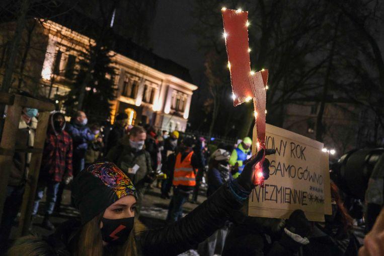 Een demonstrant toont een bliksemschicht, het teken van de vrouwenbeweging in Polen, uit protest tegen de aangekondigde strenge abortuswetgeving in het land. Beeld Getty Images