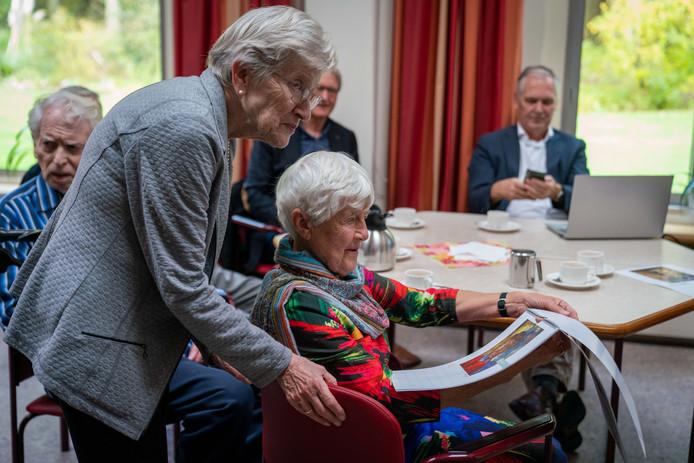 Erna (links) en Nellie Breed bekijken in Missiehuis Vrijland de kunstkalender, met daarin twaalf kunstwerken van hun overleden broer Kees.