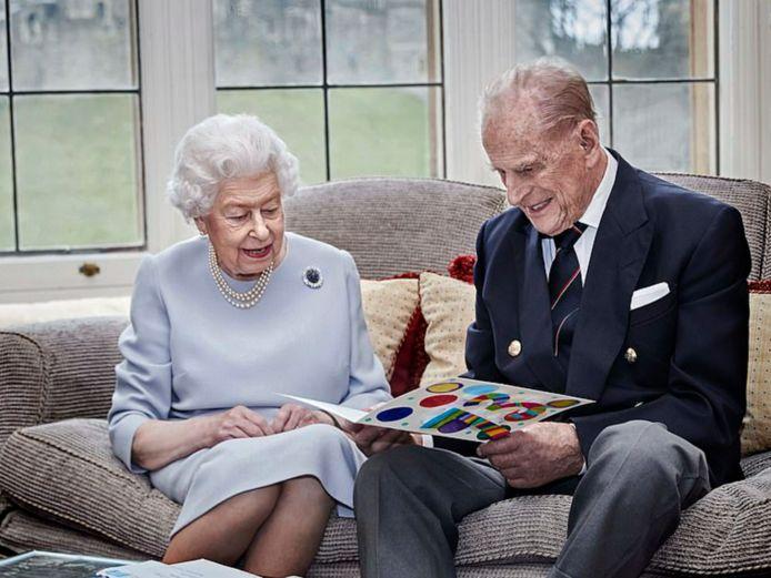 De queen en prins Philip bekijken een kaartje van hun kleinkinderen.