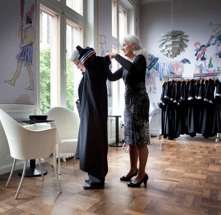 Opening Academisch jaar. In een kamer van het Academiegebouw van de Universiteit Utrecht helpt de Pedel een hoogleraar in haar toga. Beeld Maarten Hartman