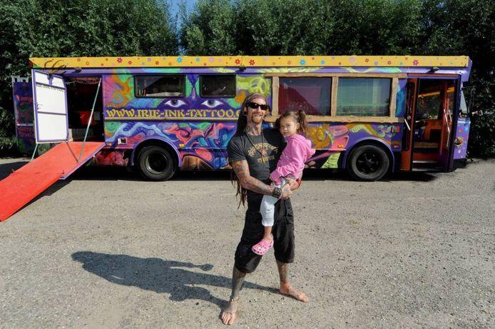 Silas van Gemert met zijn dochtertje Myla voor de tattoobus. Het voertuig dat vroeger in België in gebruik was als stadsbus, is aan een tweede leven begonnen
