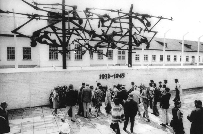 Archieffoto: Verslaggevers verzamelen zich bij de herdenking muur tijdens het bezoek dat zij vandaag aan het in de Tweede Wereldoorlog gebruikte concentratiekamp Dachau brachten. Er was speciaal gelegenheid geboden tot het bezoeken aan dit kamp voor de journalisten die de Olympische Spelen in Munchen verslaan. Op de achtergrond een van de blokken waar voor en tijdens de oorlog de gevangenen verbleven.