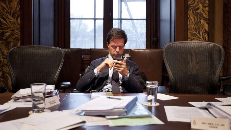 Premier Mark Rutte leest de berichten op zijn telefoon na afloop van het eerste termijn van de Algemene Politieke Beschouwingen in de Eerste Kamer in Den Haag. Beeld ANP